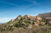 stock photo of wispy  - The mountain village of Speloncato in the Balagne region of north Corsica against a blue sky and wispy clouds - JPG