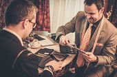 picture of tailoring  - Tailor and client choosing cloth and buttons for custom made suit - JPG