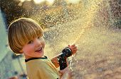 pic of sprinkler  - A young boy playing with a garden sprinkler - JPG