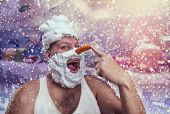stock photo of shaved head  - Smiling man with shaving foam points at his carrot nose over winter background - JPG