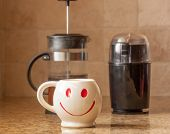 pic of taupe  - Brewing a cup of coffee with bean grinder and french press for smile face mug - JPG