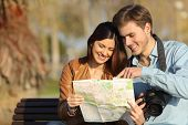 stock photo of bench  - Happy tourists searching landmarks in a map sitting on a bench outdoors - JPG