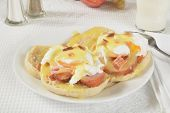 image of benediction  - Eggs Benedict topped with bacon bits and a glass of milk - JPG