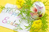image of decoupage  - Hand painted decoupage Easter egg on red surface with a Happy Easter card and two yellow chickens  - JPG