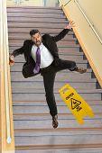 stock photo of slip hazard  - Mature Hispanic businessman falling on stairs - JPG