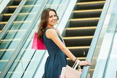 stock photo of escalator  - Rear view of beautiful young woman with shopping bags on mall escalator - JPG