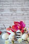 pic of figurine  - Small White Rabbit Figurine with Easter Eggs Surrounded by Pink Blossoms on Rustic Wooden Background with Copy Space Above - JPG