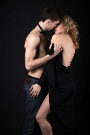 foto of half naked  - Steamy scene beautiful sexy young couple foreplay half naked man in jeans and bow tie taking off his lady evening dress after posh party studio black background - JPG