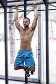 stock photo of pull up  - Front view of a muscular man doing pull up exercises - JPG