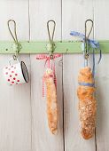 image of hook  - Artisan French baguette breads wrapped with ribbons hanging on a vintage clothes hook - JPG