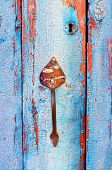 picture of keyhole  - Old tacky blue door with vintage handle and keyhole - JPG