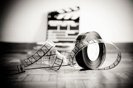 image of mm  - 35 mm cinema film reel and out of focus movie clapper board in background on wooden floor in vintage black and white - JPG
