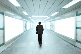 image of underpass  - Rear view businessman walking through bright underpass with blank billboard advertising wall - JPG