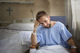 pic of medical condition  - young injured man in hospital room sitting alone in pain looking negative and worried for his bad health condition sitting on chair suffering depression on a sad lonely medical background - JPG
