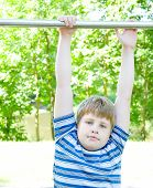 A Little Boy Hangs On A Horizontal Bar In A Summer Park.