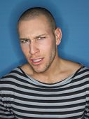 Man in stripy top frowning in studio