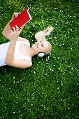 picture of young girls  - Woman lying on grass with book and headphones - JPG