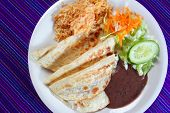 quesadillas rice salad frijoles sauce Mexican food on blue serape