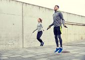 fitness, sport, people, exercising and lifestyle concept - man and woman skipping with jump rope out poster