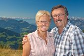 Senior couple hiking in the mountains over blue sky
