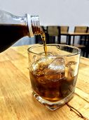 Cola In Glass Ice, Pouring Cola From Glass Bottles Drinks To A Glass With Ice Cubes, Cola In Glass I poster