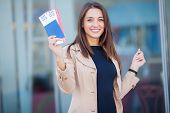 Image Of European Woman Having Beautiful Brown Hair Smiling While Holding Passport And Air Tickets poster