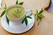 Marijuana Tea. Hemp Tea. Cannabis Tea in a White Tea Cup with a Marijuana Leaf and Stem with Flowers poster