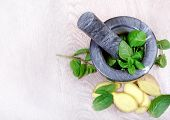Stone Pestle And Mortar With Mint Leaves And Ginger On A Wooden Table. Top View. Cold And Flu Remedy poster