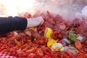 A Hand Reaching Into A Pile Of Steaming Food Piled On A Table At A Crawfish Boil And Grabbing A Saus poster
