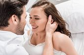 Man Tenderly Touching Face Of Beautiful Smiling Woman In Bed poster