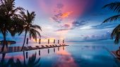 Luxury Infinity Pool Overlooking Sunset Sea And Sky Reflection. Amazing Swimming Pool And Beach Back poster