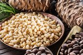 Pine nuts in the bowl and pine nut cone on the wooden table. Organic food. poster