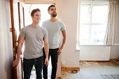 Excited Male Couple Opening Front Door Of New Home poster