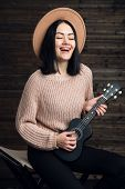 Attractive Emotional Young Caucasian Woman In Sweater And Hat Singing Passionately And Playing Ukule poster