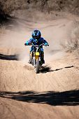 stock photo of moto-x  - Vertical image of a young boy motor cross racer riding a yellow dirt bike in the desert - JPG