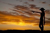 stock photo of cowgirl  - a silhouette of a cowgirl holding on to her guns pointing it at something - JPG