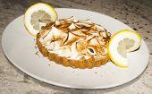Lemon meringue tart on white plate with lemon slices