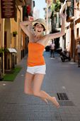 Exuberant Young Woman Jumping For Joy