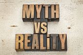 myth versus reality - concept  in vintage letterpress wood type on a grunge painted barn wood backgr