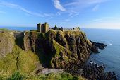 stock photo of promontory  - Dunnottar Castle with blue sky background in Aberdeen Scotland - JPG