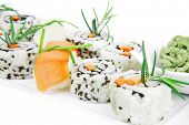 Roll with Cucumber , Cream Cheese with raw Tuna and Salmon inside. on long white plate . Isolated ov