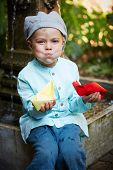 image of wet pants  - Little four year old boy in a blue outfit playing with paper boats in a small outdoor water fountain - JPG