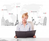 Beautiful young businesswoman with world map and major landmarks of the world poster