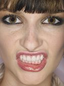 Extreme closeup of a beautiful angry young woman clenching teeth