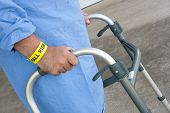 stock photo of hospital gown  - A hospital patient wearing a fall risk bracelet using a walker