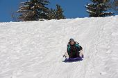 stock photo of toboggan  - Smiling girl toboggans down a snowy hill in the sunshine - JPG