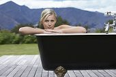 image of bathtime  - Portrait of a beautiful woman in bathtub on porch against mountains - JPG
