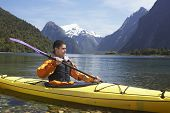 stock photo of canoe boat man  - Young man kayaking in peaceful lake with mountains in background - JPG