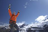 Male mountain climber raising hands with arms raised against snowy mountains