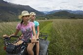 Two young women riding a four wheeler through field